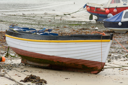 fibreglass: Small white fishing boat on sand at low tide
