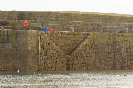 mousehole: Sea wall steps in Mousehole harbour, Cornwall, England