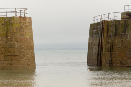 mousehole: Entrance in sea wall from sea to Mousehole harbour, Cornwall, England