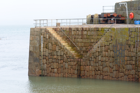 mousehole: Steps on Mousehole harbour wall, Cornwall, England Stock Photo