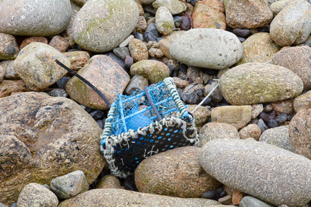 lobster pot: Lobster pot on rocks on beach Stock Photo