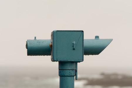 far away look: Blue telescope at seaside on rainy day Stock Photo