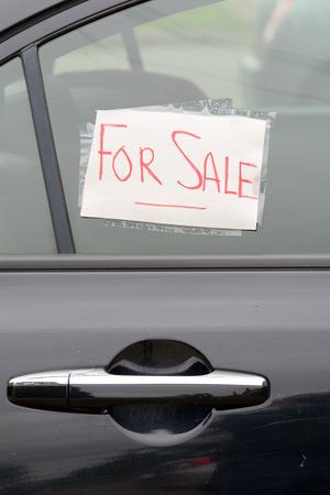 handwritten: For Sale sign on car window - handwritten