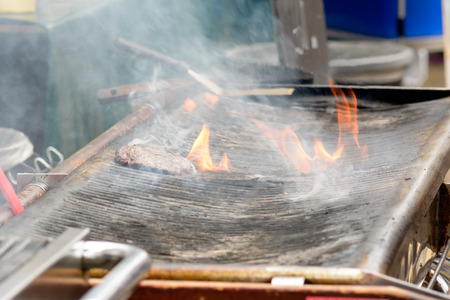 beefburger: Beefburger cooking on grill with flames Stock Photo