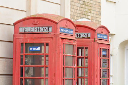 Two red phone boxes with email text phone signs
