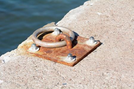 Metal boat mooring ring on sea wall