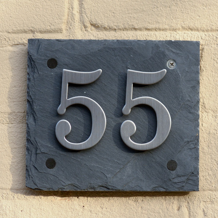 house walls: House number 55 sign