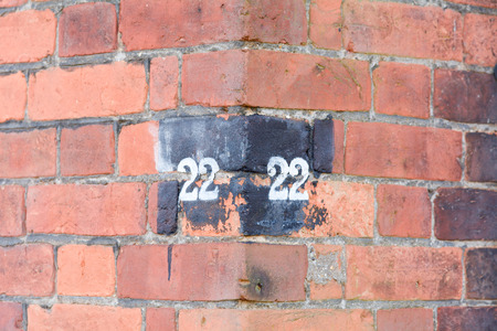 house  houses: House number 22 sign on corner of wall