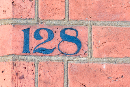 white house: House number 128 painted sign