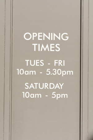 time's: Shop opening times on wall Stock Photo