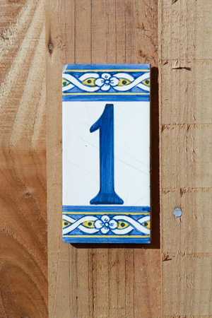1: House number 1 sign on fence