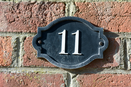 inform information: House number 11 sign on wall Stock Photo