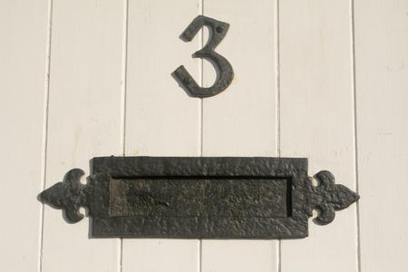 number 3: House number 3 sign on door