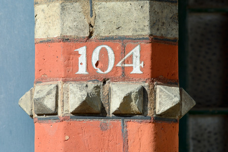 inform information: House number 104 painted sign Stock Photo