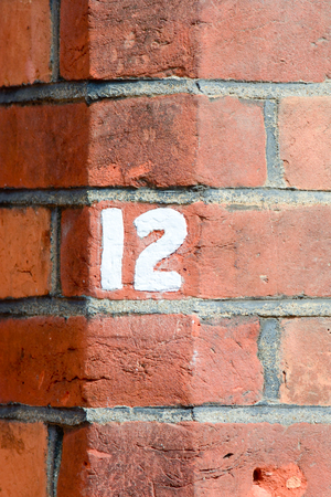 number 12: House number 12 painted sign on wall Stock Photo