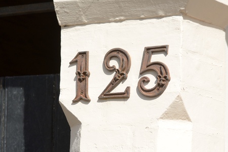 House number 125 sign on wall