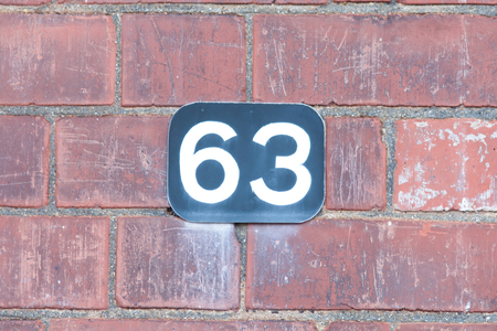 inform information: House number 63 painted sign Stock Photo