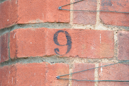 inform information: House number 9 painted sign Stock Photo