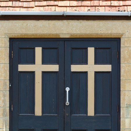 congregation: Christian Cross on doors to Church Stock Photo