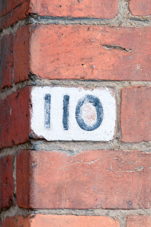 inform information: House number 110 painted sign Stock Photo