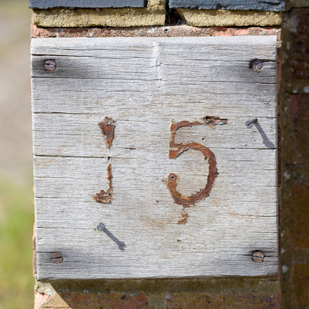number 15: House number 15 faded sign
