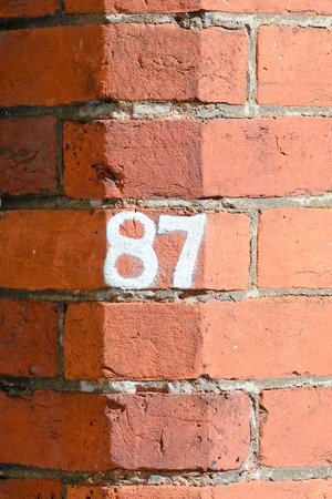 inform information: House number 87 painted sign Stock Photo
