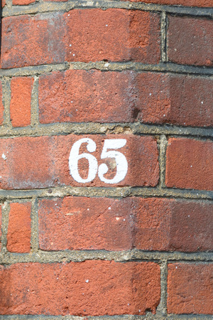 inform information: House number 65 painted sign