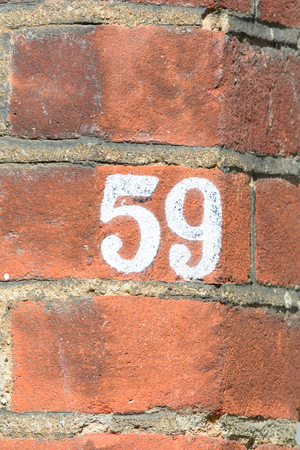 inform information: House number 59 painted sign Stock Photo