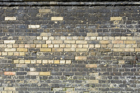 ensuring: New bricks in wall to replace damaged section Stock Photo
