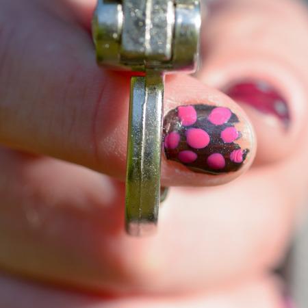 gatillo: Mujer con las uñas pintadas con el dedo en el gatillo de pistola