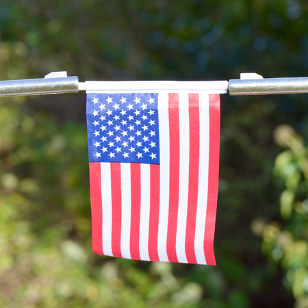 US Flag held between two gun barrels - comment on US gun control Stock Photo