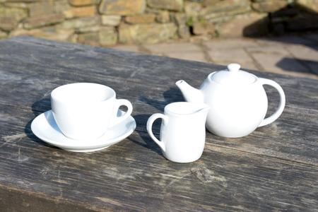 traditonal: Tea pot tea cup and saucer plus a milk jug on wooden cafe table