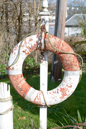 Old red and white painted life saver ring being used as a decorative piece in a garden Stock Photo