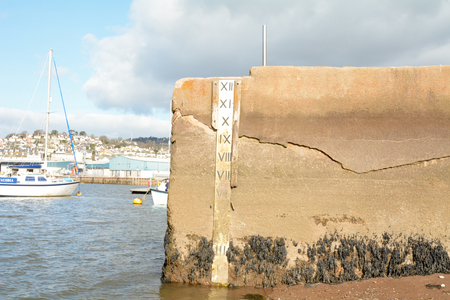 depth measurement: Water depth marker with depth in feet on sea wall in Teignmouth Devon England
