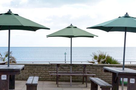 greeen: Cafe tables with greeen umbrellas at seaside Stock Photo