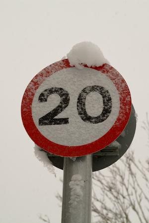 20 mph speed limited sign obscured by snow Stock Photo