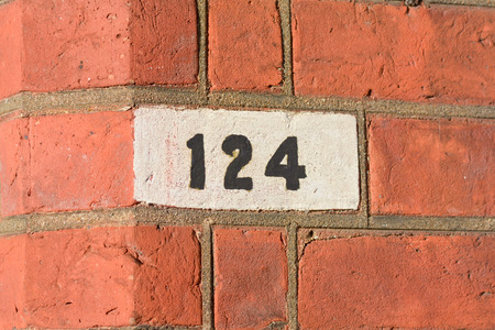 House number 124 painted sign on wall