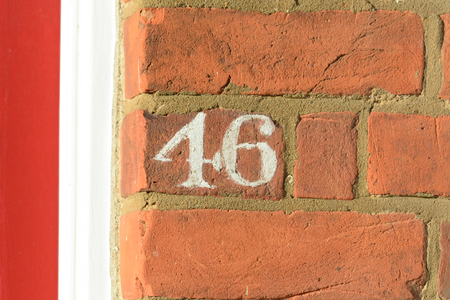 House number 46 painted sign on wall