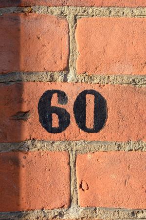 House number 60 sign painted black on red brick wall Reklamní fotografie