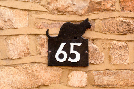 House number 65 sign with blkack cat shape
