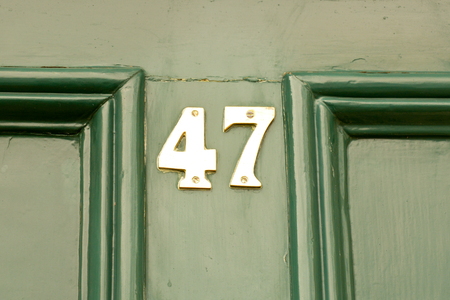 House number 47 sign on green door Stock Photo