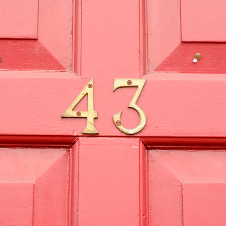 House number 43 sign on red door Stock Photo