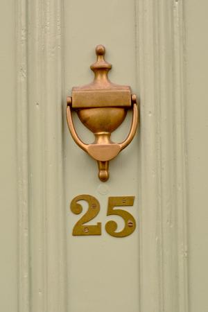 House number 25 sign on green door with brass door knocker