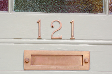 House number 121 sign and letterbox on door Stock Photo
