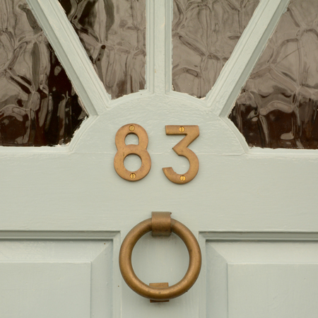 House number 83 sign on door with brass knocker