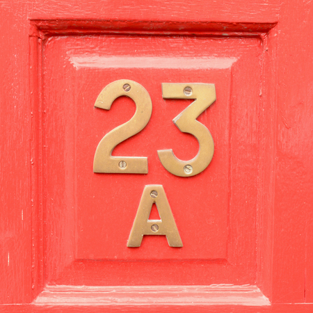 House number 23a sign on red door