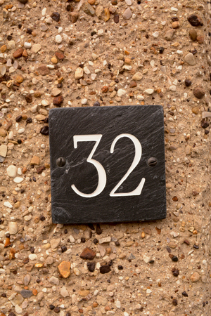 House number 32 sign on wall Stock Photo