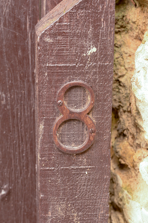House number 8 sign on wooden gate post