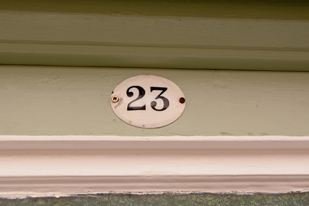House number 23 sign on door frame Stock Photo
