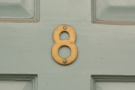 House number 8 sign on green door